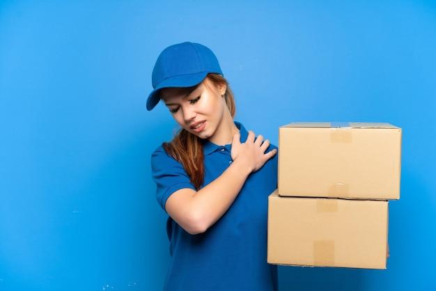 Доставка девушка через изолированную синюю стену страдает от боли в плече из-за того, что приложила усилие