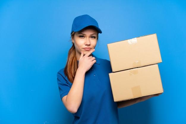 Доставка девушка над изолированной синей стеной мышления