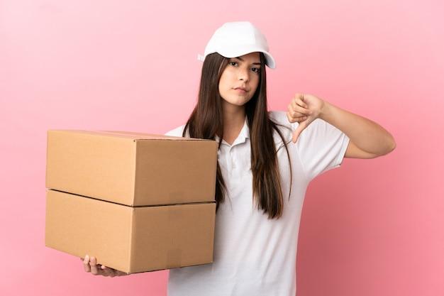 부정적인 표정으로 엄지손가락을 아래로 보여주는 고립 된 분홍색 벽 위에 배달 소녀