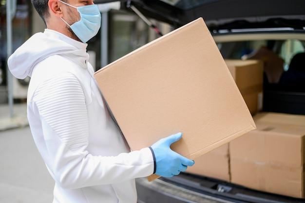 Парень доставки несет картонную коробку