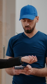 Delivery guy holding contactless pos terminal service delivering takeaway food order giving to businesswoman in startup company office. entrepreneur client paying meal ordered using smartwatch