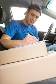 Доставка парень в машине с коробкой