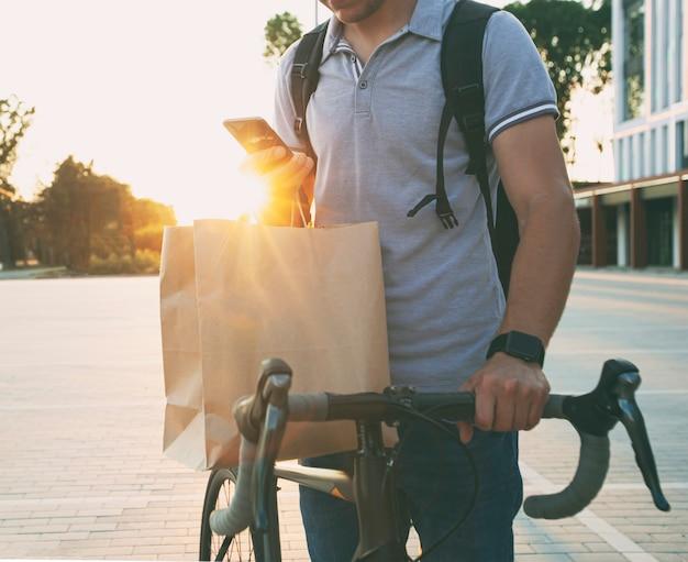 Парень из службы доставки на велосипеде, ожидая, пока покупатель отдаст заказ