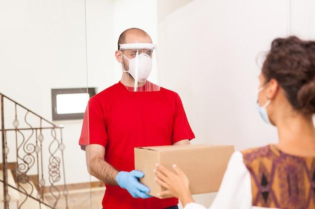 顧客のための保護マスク保持ボックスを身に着けている配達人。
