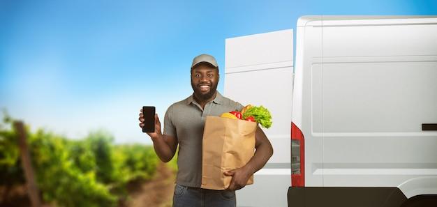 製品が到着する菜園で食べ物でいっぱいの食料品の袋を持った配達人