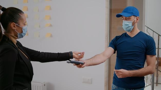 会社のオフィスでランチタイムに持ち帰り用のフードボックスを配達する保護フェイスマスクと手袋を持つ配達人