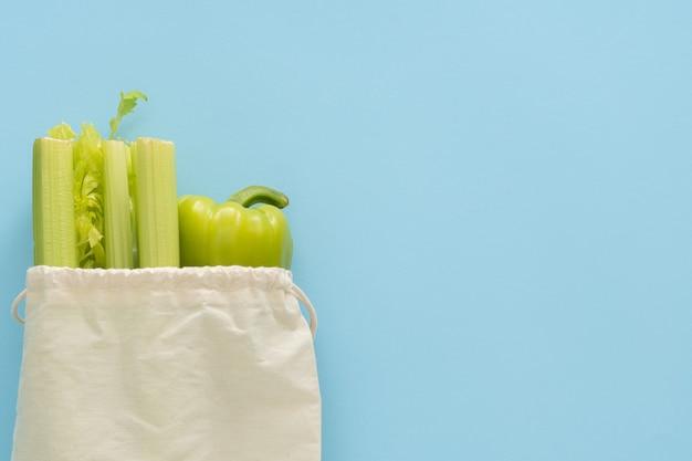 Доставка здоровой пищи фон. вегетарианские вегетарианские блюда в эко-хлопковых мешках с овощами на синем фоне. продуктовый супермаркет и концепция чистой еды. вид сверху. место для текста