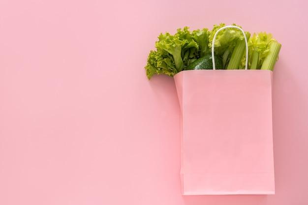 Доставка здоровой пищи фон. вегетарианские вегетарианские блюда в овощах бумажного мешка на розовом фоне. продуктовый супермаркет и концепция чистой еды. вид сверху. место для текста