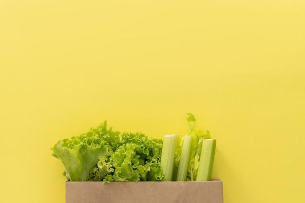 Доставка здоровой пищи фон. вегетарианские вегетарианские блюда в овощах бумажного пакета на желтом фоне. продуктовый супермаркет и концепция чистой еды. вид сверху. место для текста
