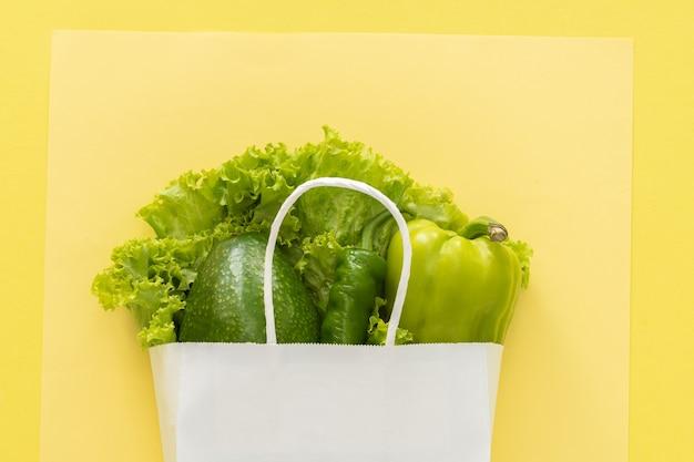 Доставка здоровой пищи фон. вегетарианские вегетарианские блюда в белом бумажном пакете овощей на желтом фоне. продуктовый супермаркет и концепция чистой еды. вид сверху. место для текста