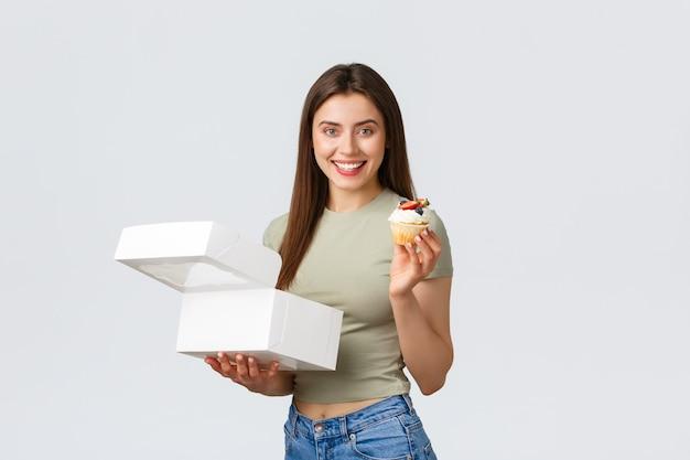 배달, 라이프 스타일 및 음식 개념입니다. 제과점과 컵케이크에서 열린 상자를 들고 서 있는 쾌활한 행복한 예쁜 여성, 택배 주문을 받고 맛있는 음식을 먹고 카메라를 보며 웃고 있습니다.