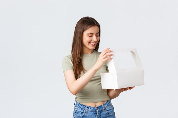 배달, 라이프 스타일 및 음식 개념입니다. 행복한 여성 고객은 좋아하는 카페나 레스토랑에서 주문을 받고 디저트, 케이크 또는 머핀, 흰색 배경이 있는 흰색 상자를 엽니다.