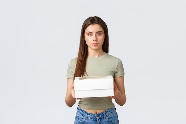 배달, 라이프 스타일 및 음식 개념입니다. 컵케이크가 든 상자를 들고 있는 세련된 젊은 예쁜 여성, 좋아하는 카페에서 주문한 디저트. 소녀는 레스토랑에서 택배를 받습니다.
