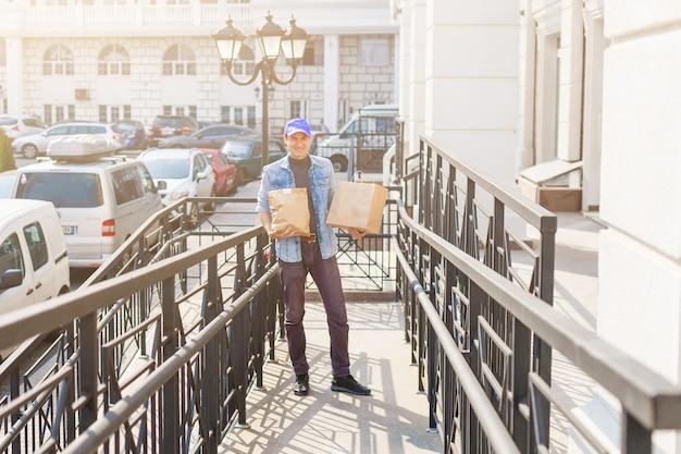 배달, 우편, 사람 개념 - 1회용 종이 봉지에 담긴 커피와 음식을 고객의 집으로 배달하는 남자