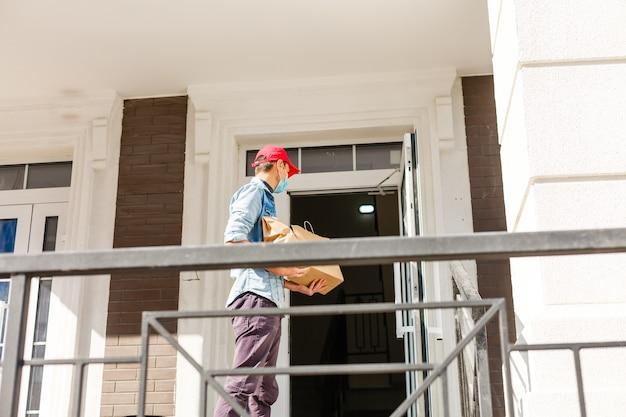 배달, 우편, 사람 개념 - 보호용 마스크를 쓴 남자가 일회용 종이 봉지에 담긴 커피와 음식을 고객의 집으로 배달합니다