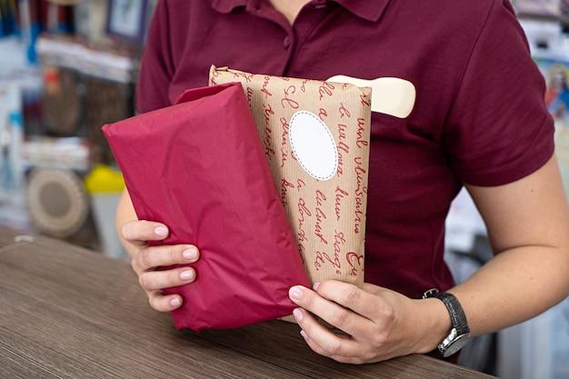 配達郵便郵便郵便パッケージ赤とクラフト紙箱を手に