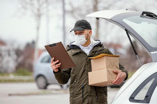マスクとパッケージの配達男性