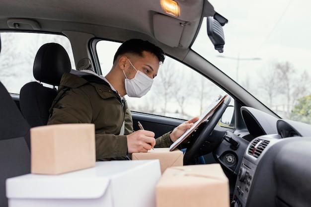 Мужчина доставки с маской и пакетами