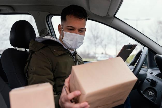 Consegna maschio con maschera e pacchi