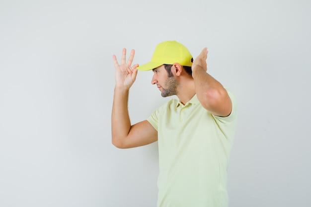 配達人は黄色い制服を着てキャップを調整し、ハンサムに見えます。正面図。