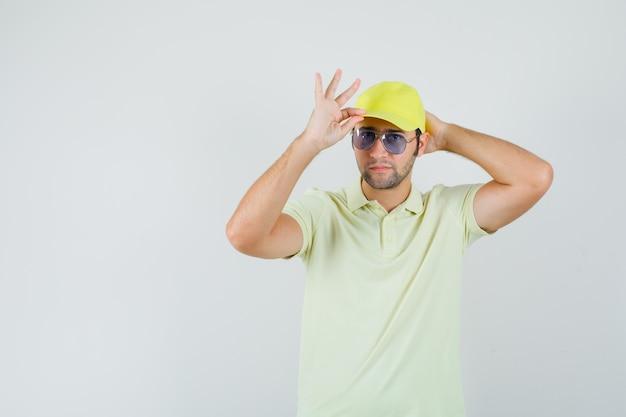 Fattorino che si aggiusta il berretto in uniforme gialla e sembra bello. vista frontale.
