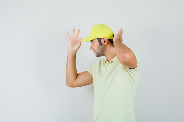 Delivery man adjusting his cap in yellow uniform and looking handsome. front view.
