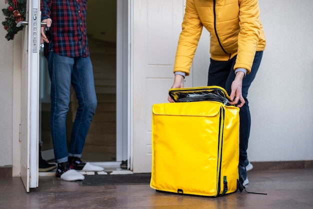 黄色のバックパックを開く冬の配達人と出入り口に立っているクライアント