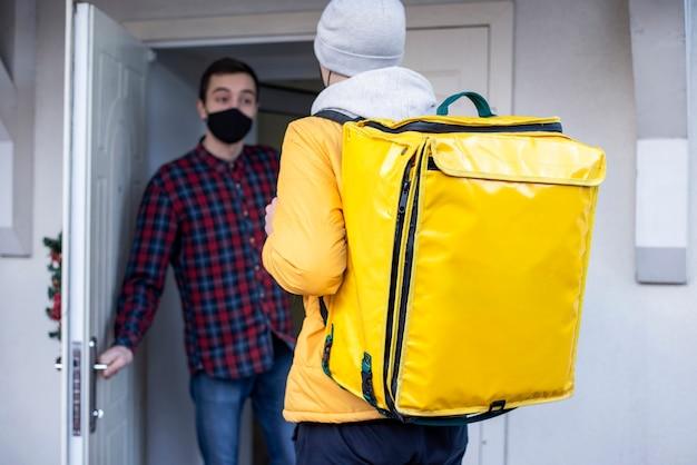 黄色のバックパックとクライアントが戸口に立っている冬の配達人