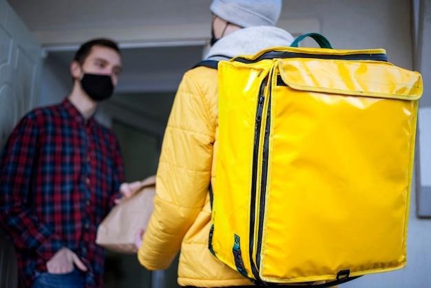노란색 배낭 겨울에 배달원이 출입구에 서있는 고객에게 주문을 제공합니다.