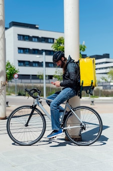 Delivery man on bicycle operated the order in the app