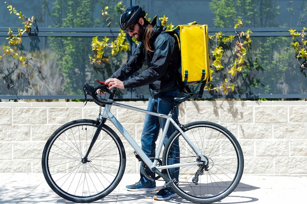 Delivery man on bike looking at smartphone