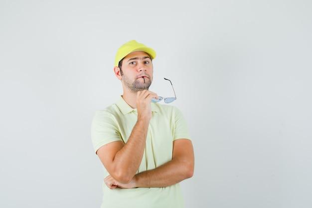 Uomo di consegna che morde gli occhiali in uniforme gialla e guardando pensieroso, vista frontale.