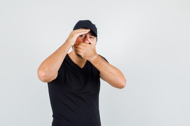 Uomo di consegna in maglietta nera, cappuccio che copre la bocca e occhi ammiccanti