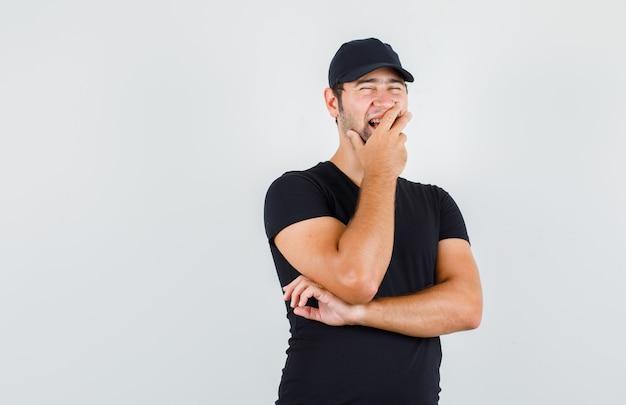 Uomo di consegna in maglietta nera, cappuccio che ride con la mano sulla bocca