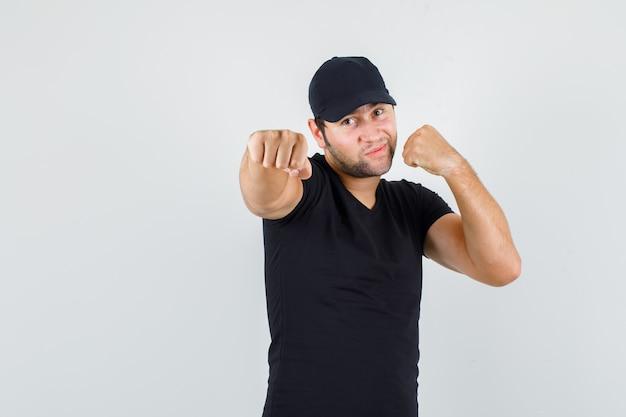 Fattorino in maglietta nera, berretto in piedi in posa boxer e guardando fiducioso