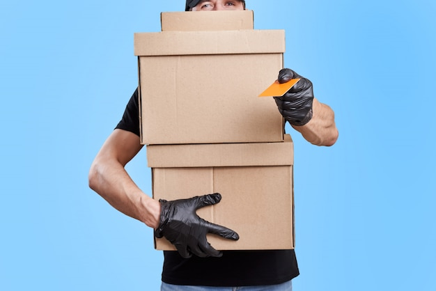 Delivery man in black uniform with medical gloves and protective mask hold cardboard box