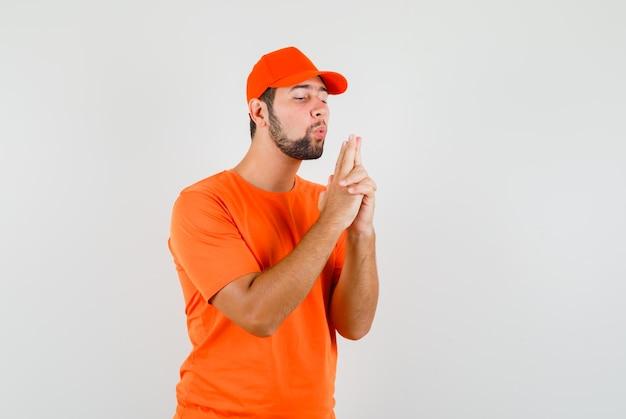 Uomo di consegna che soffia sulla pistola fatta dalle sue mani in maglietta arancione, berretto, vista frontale.