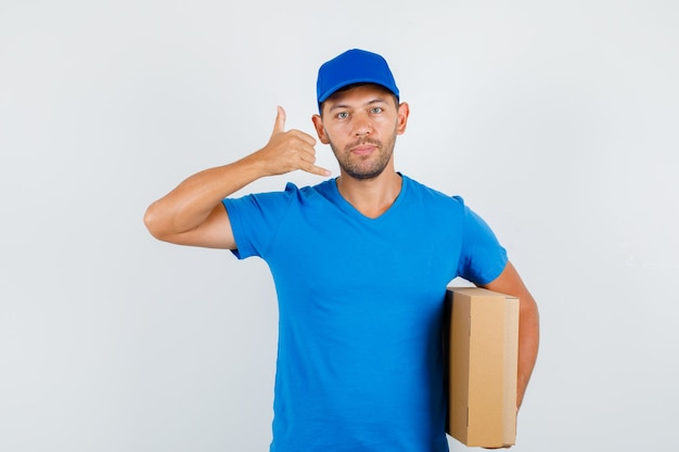 Delivery man in blue t-shirt, cap holding cardboard box with phone gesture