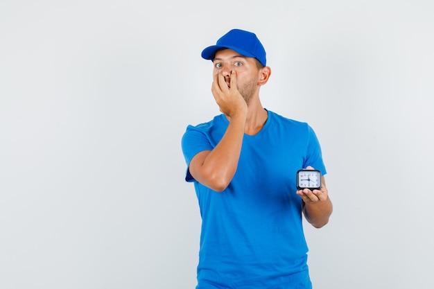 Fattorino in maglietta blu, berretto tenendo l'orologio con la mano sulla bocca e guardando eccitato