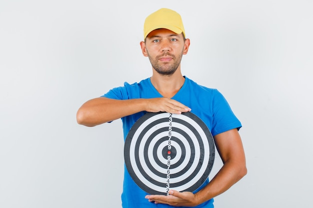 Fattorino in maglietta blu, berretto che tiene il bersaglio e che sembra positivo