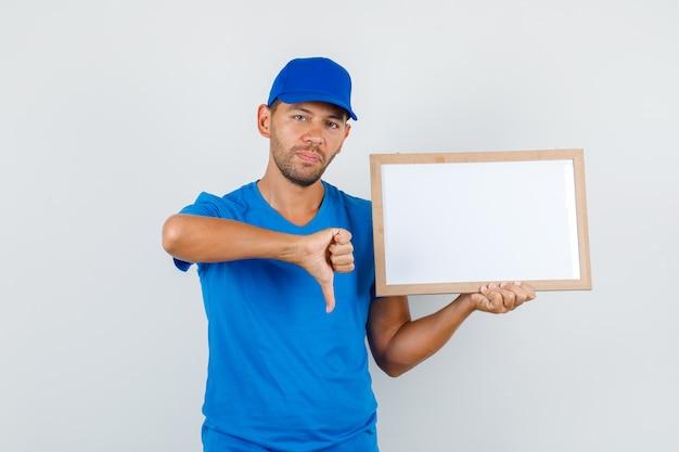 Fattorino in maglietta blu, cappuccio che tiene il bordo bianco con il pollice verso il basso
