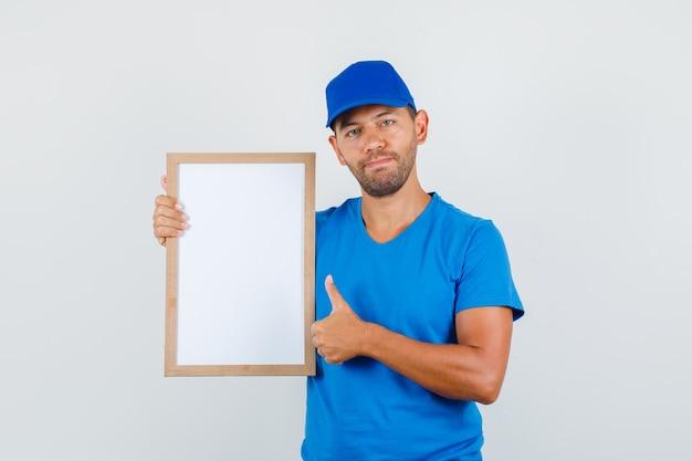 Fattorino in maglietta blu, cappuccio che tiene il bordo bianco con il pollice in su e che sembra sicuro