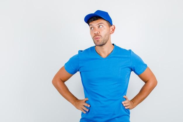 Uomo di consegna in maglietta blu, cappuccio che osserva da parte con le mani sulla vita e che sembra pensieroso