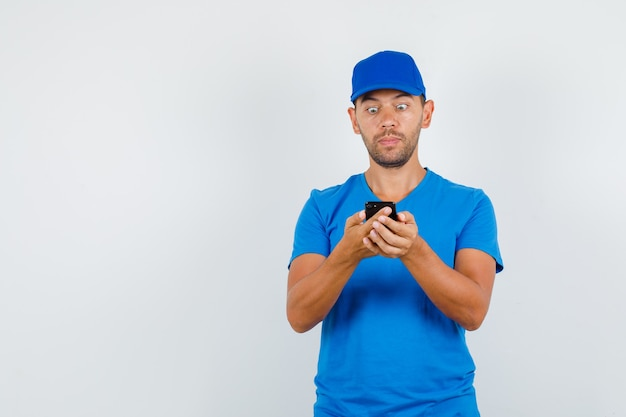 Delivery man in blue t-shirt, cap looking at smartphone and looking shocked