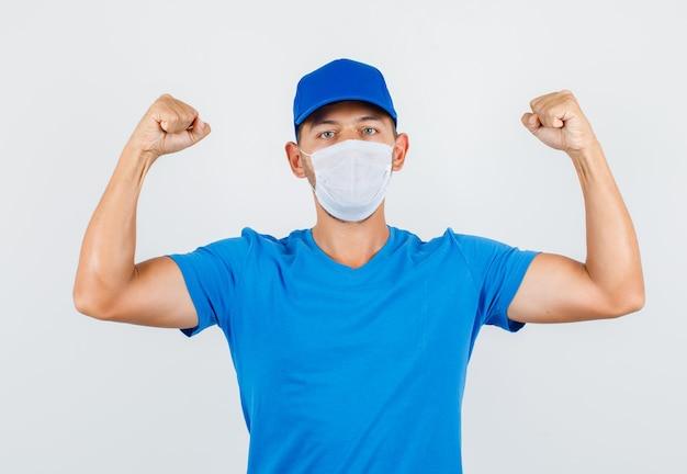 Fattorino in maglietta blu, berretto, maschera che mostra i muscoli e sembra forte