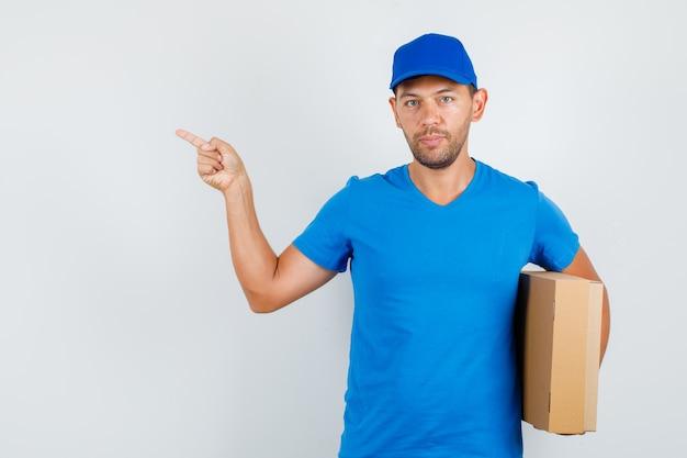 Fattorino in maglietta blu, cappuccio rivolto lontano mentre si tiene la scatola di cartone