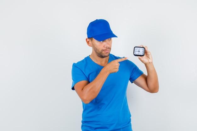 Fattorino in maglietta blu, berretto puntare il dito contro l'orologio