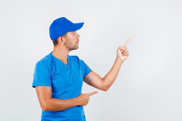 Fattorino in maglietta blu, cappuccio che mostra qualcosa con le dita