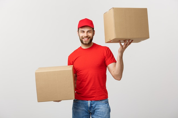 Delivery man in cap with red t-shirt working as courier or dealer holding two empty cardbo