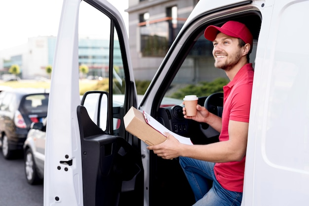 Delivery man in car with coffee